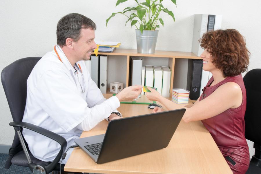 Kobieta płaci za wizytę u lekarza