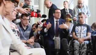 Premier Mateusz Morawiecki (C) i minister rodziny, pracy i polityki społecznej Elżbieta Rafalska (L) spotkali się z uczestnikami stacjonarnego protestu rodziców osób niepełnosprawnych w Sejmie