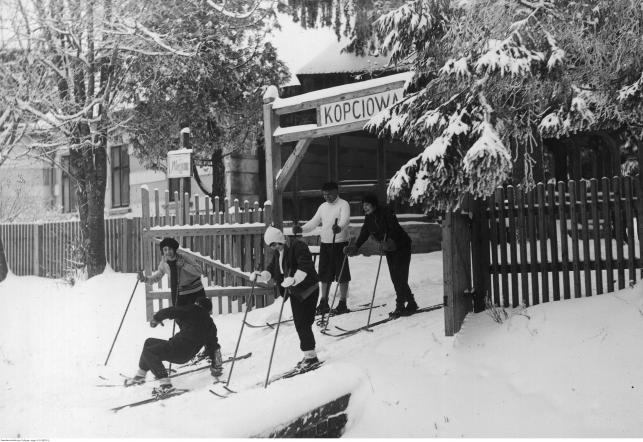 Grupa turystów na nartach przed drewnianą bramą