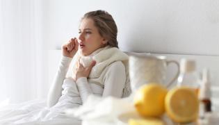 Chora kobieta w łóżku kaszle