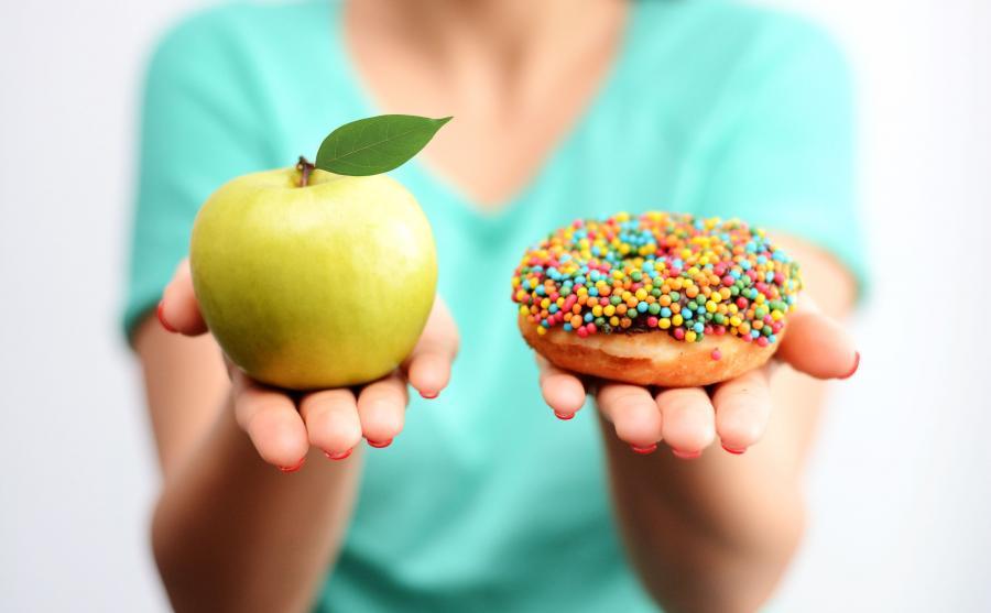 Kobieta trzyma jabłko i donata