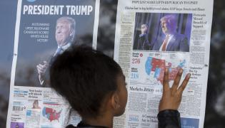 Afroamerykańskie dziecko czyta o zwycięstwie Donalda Trumpa w wyborach prezydenckich