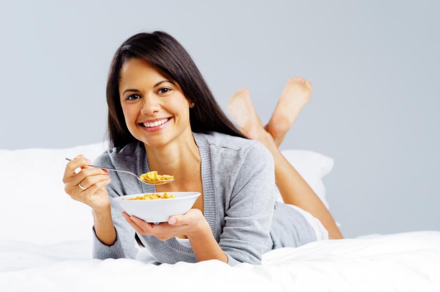 Kobieta jedząca śniadanie w łóżku