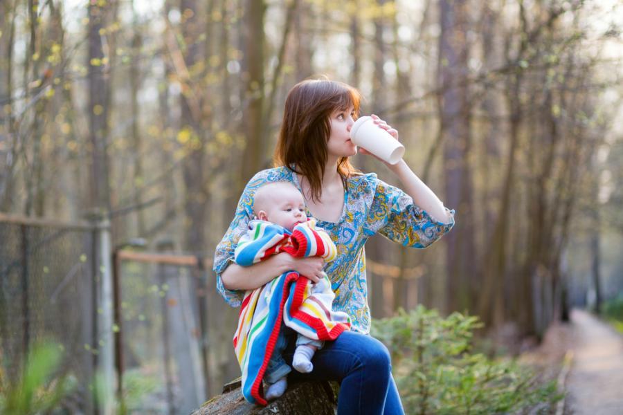 Matka z dzieckiem i kubkiem kawy w ręku