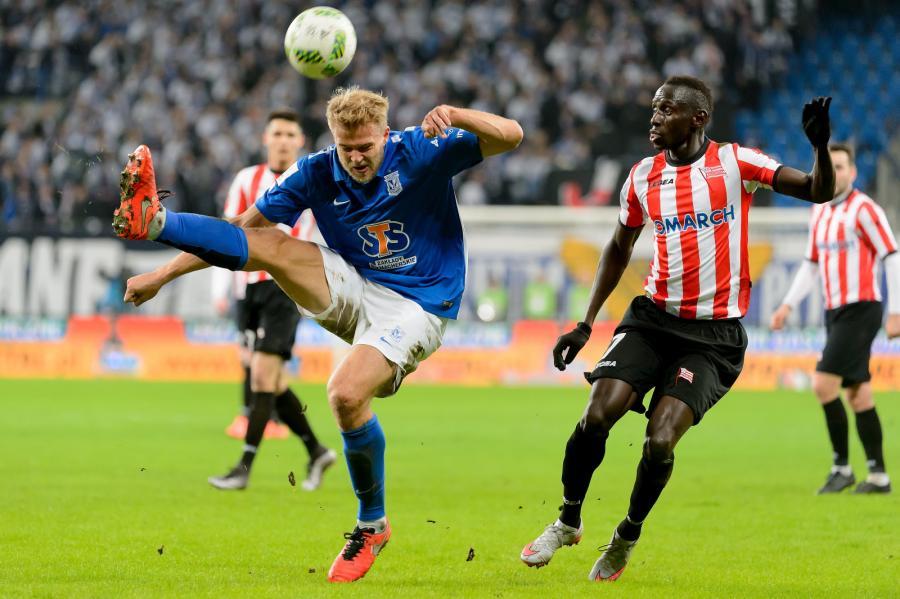Zawodnik Lecha Poznań Paulus Arajuuri (L) walczy o piłkę z Boubacarem Diabangiem (P) z Cracovii podczas meczu polskiej Ekstraklasy